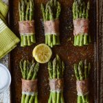 6 proscuitto wrapped asparagus bundles on a cookie sheet with half a squeezed lemon in the middle of the cookie sheet.