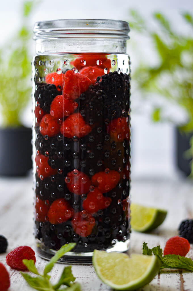A jar of white rum with raspberries and blackberries in a jar. Greenery is in the background with lime wedges next to the jar.