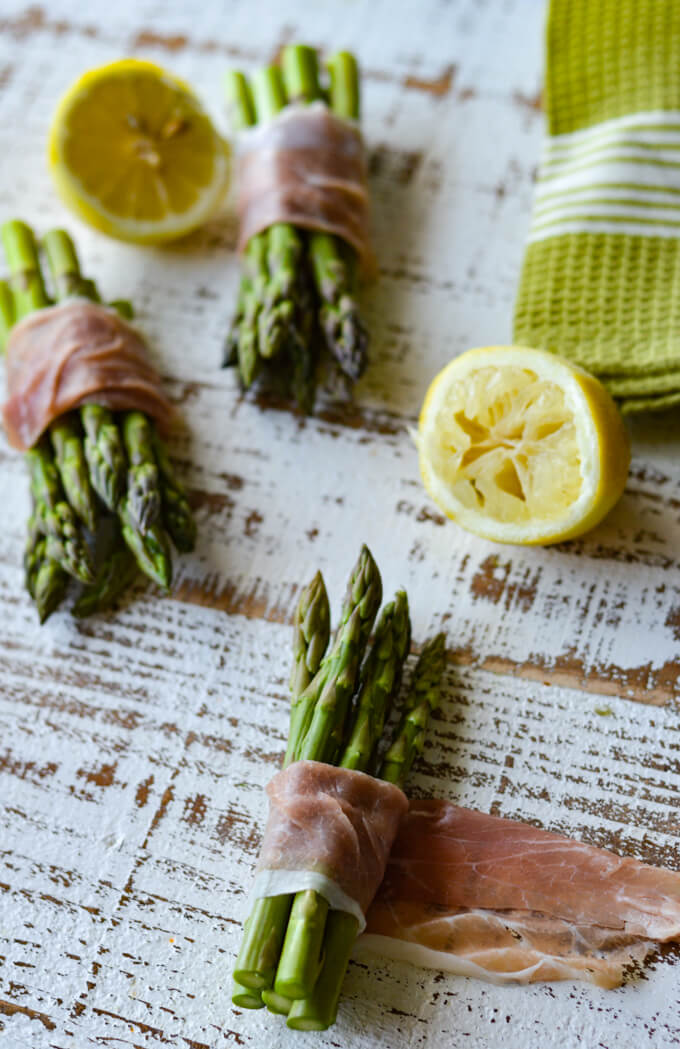 Small asparagus bundles wrapped with prosciutto with squeezed lemon halves and a green napkin.