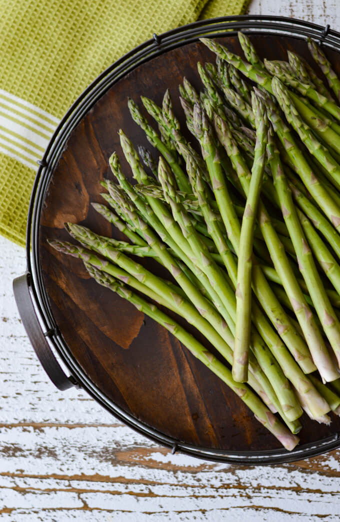Prosciutto Wrapped Roasted Asparagus Bundles - a lot of asparagus on a wooden tray