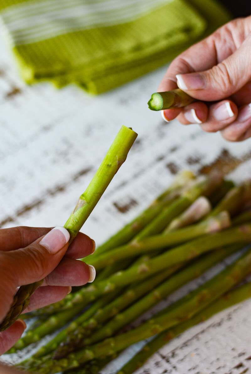 A bundle of asparagus with one piece being snapped by two hands.