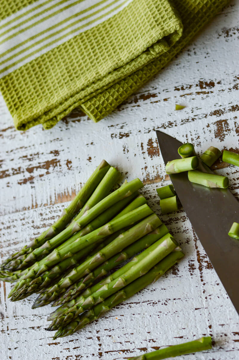 A bundle of asparagus and a knife that has cut off the ends.