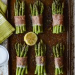 Prosciutto Wrapped Roasted Asparagus Bundles on a cookie sheet