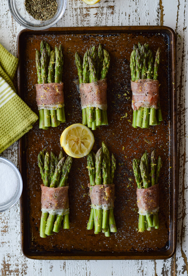 A cookie sheet with 6 bundles of asparagus wrapped with prosciutto and a squeezed lemon half in the middle of the pan.
