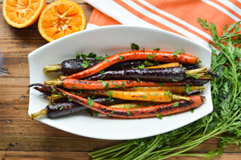 Easy Dinner Party Recipes That Will Impress your Friends - Roasted Candied Rainbow Carrots with Orange-Maple Syrup in a serving dish