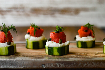 Easy Dinner Party Recipes That Will Impress your Friends - Smoked Salmon and Cream Cheese Timbales with Cucumbers on a wooden tray