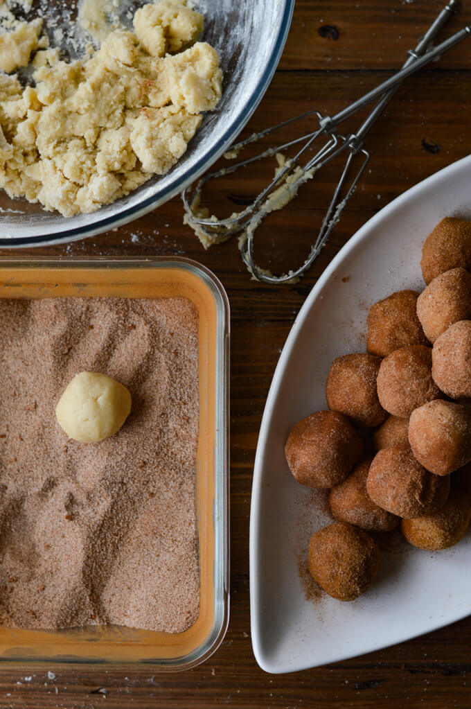 Unbaked snickerdoodle cookie balls rolled in cinnamon and sugar on a white plate with egg beaters and a bowl of cookie dough sitting next to them. A glass container with cinnamon and sugar sits next to it with one cookie dough sitting it the container.