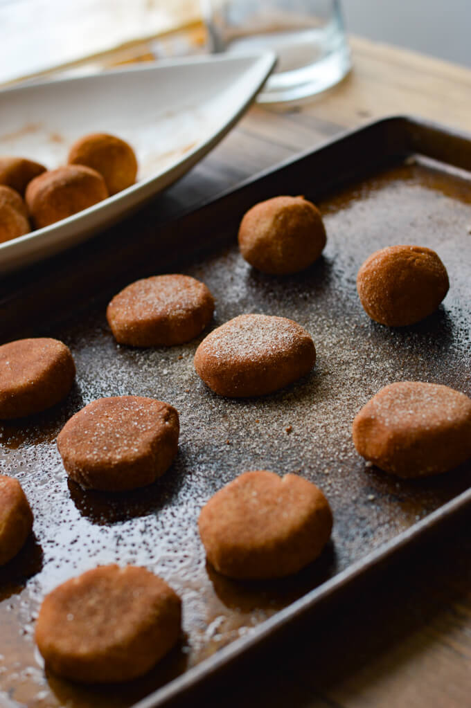 A cookie sheet with unbaked snickerdoodle cookies on it and a white plate sits next to it with more cookie dough balls in it.