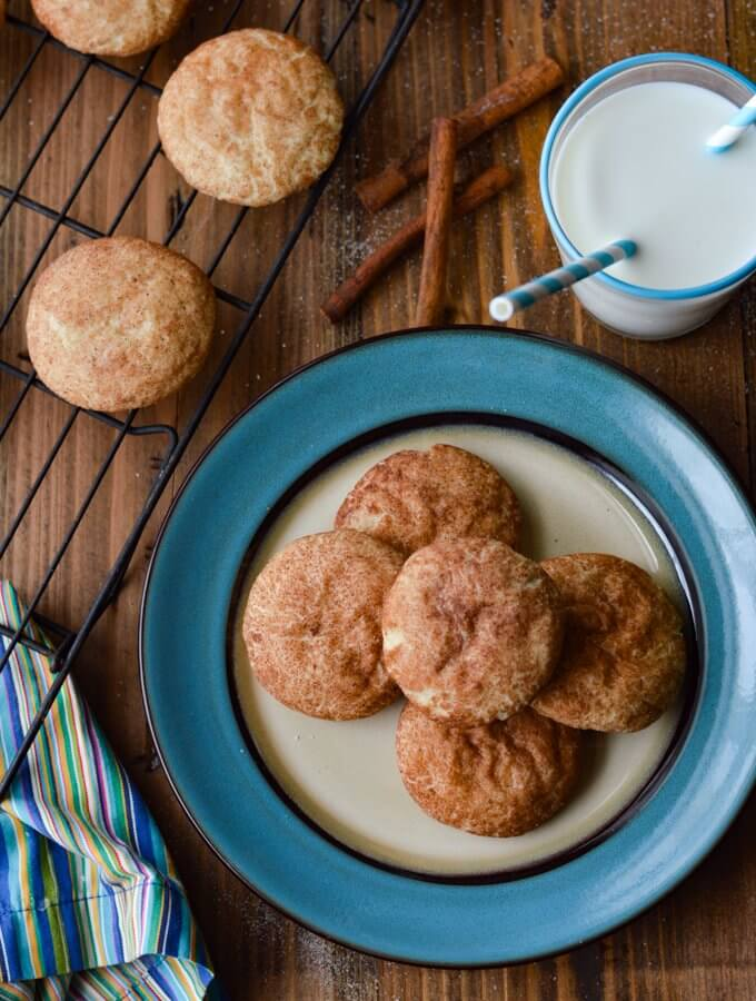 A blue plate of snickerdoodle coolies and a glass of milk with a blue and white striped straw. 3 cinnamon sticks lay next to them along with a wire rack of cooking snickerdoodle cookies.