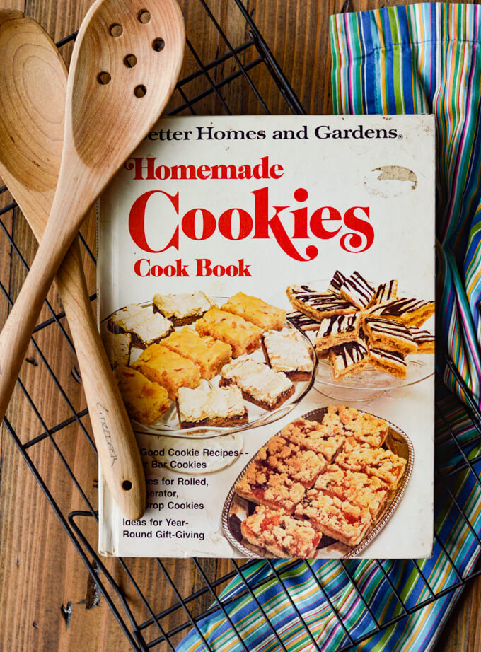 A cookies cookbook on a wire baking rack with wooden spoons sitting next to them. There's a blue striped napkin next to them.