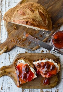 Homemade White Peach Preserves with Cherries and Pecans on crusty bread with butter