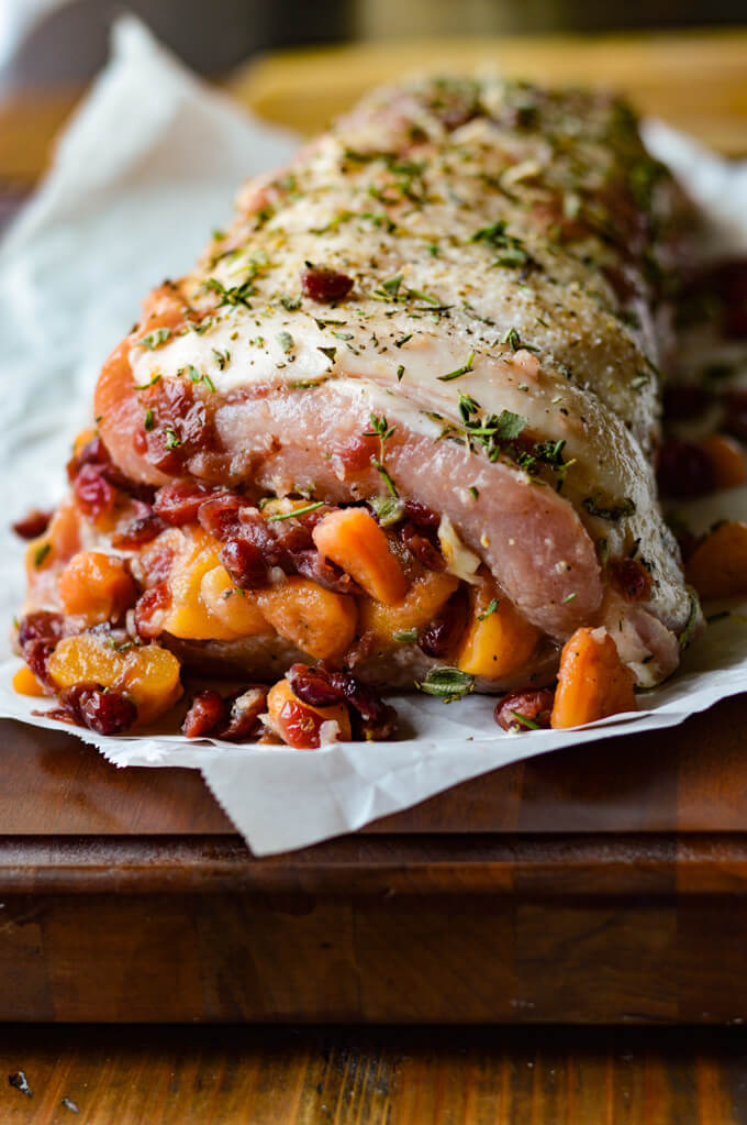 A front view of a raw pork loin roast rolled up with fruit stuffing in it and fresh herbs sprinkled on top.