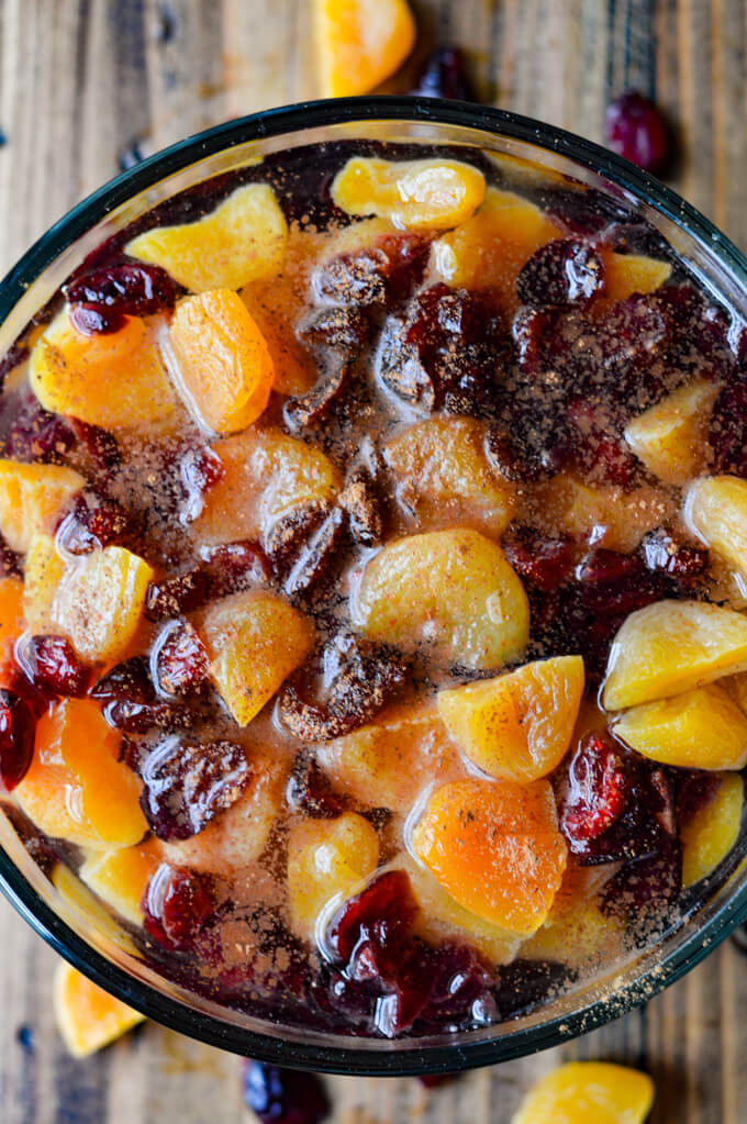 A clear glass bowl of dried apricots and craisins soaking in water with cinnamon sprinkled on top.