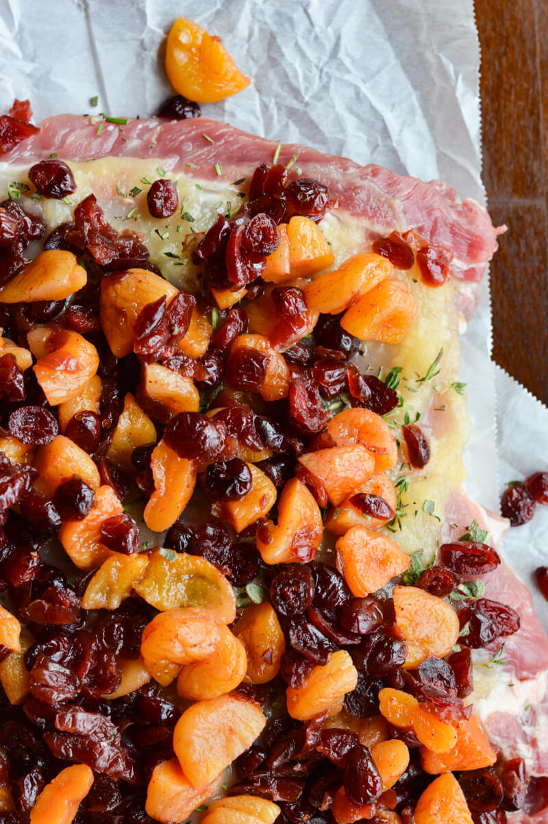 A corner of a butterflied raw piece of pork roast with applesauce, herbs and dried fruit on top.