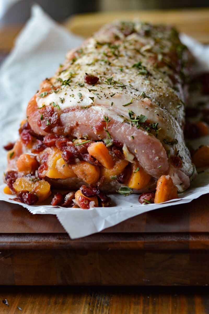 An uncooked rolled up pork roast stuffed with dried fruit and herbs.