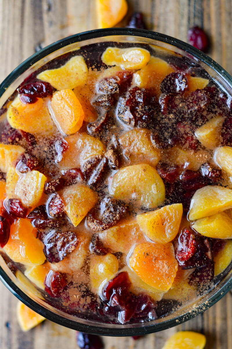 A bowl of dried fruit in water with cinnamon sprinkled on top.