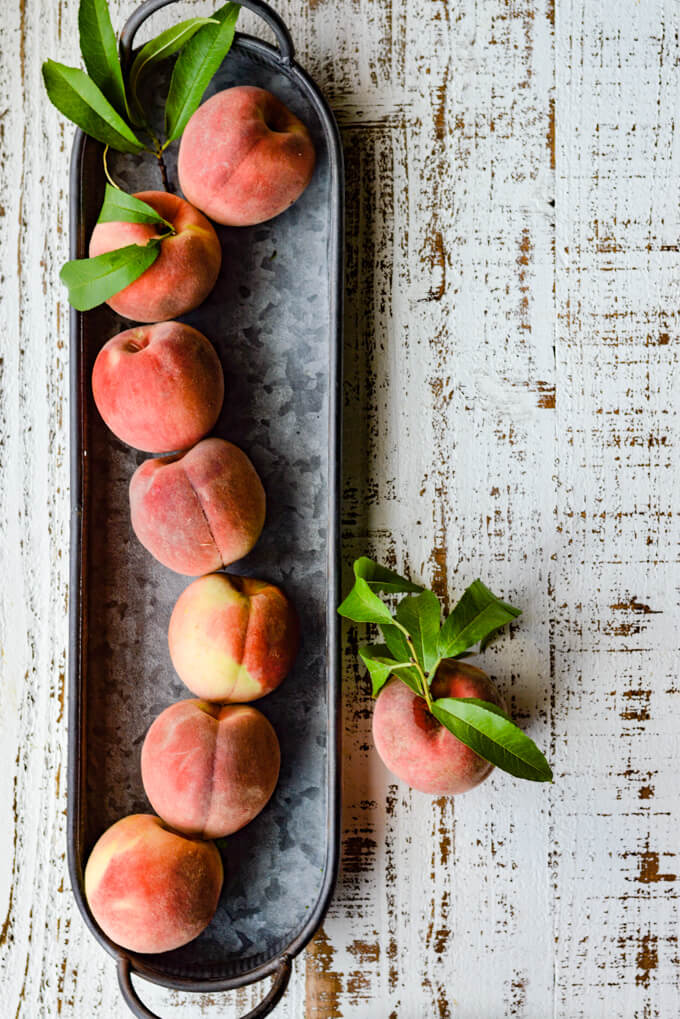 A gray tin tray holds a bunch of fresh peaches, some with leaves. Another peach sits outside the tin tray.