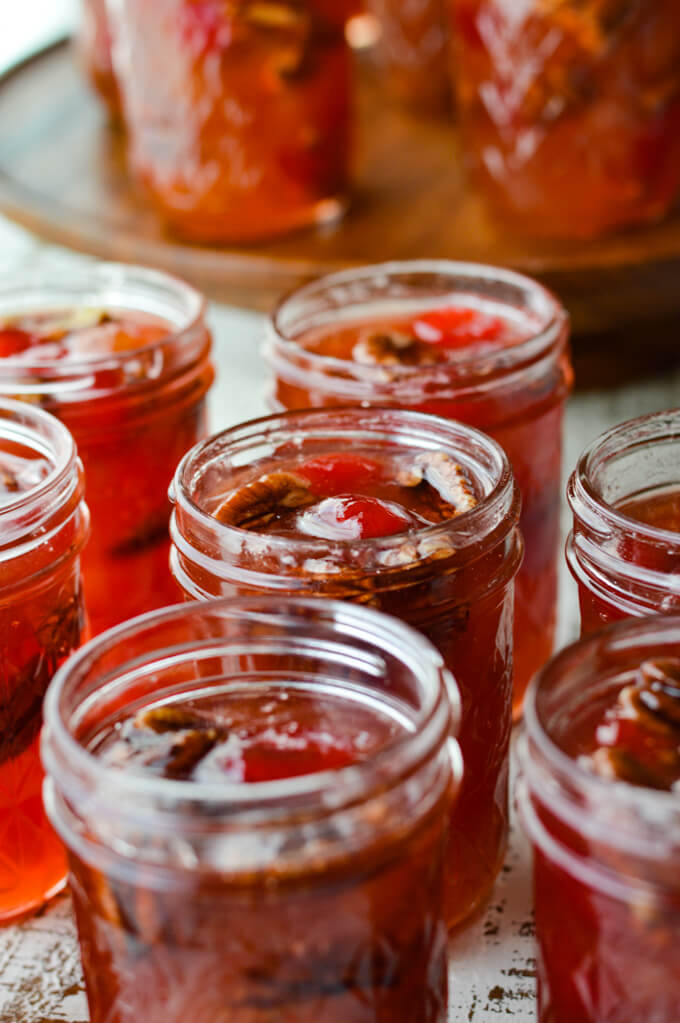 Jars of homemade peach preserves with pecans and cherries.