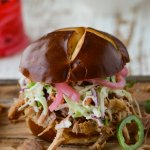 A closeup shot of a pulled pork sandwich with homemade coleslaw and pickled onions.