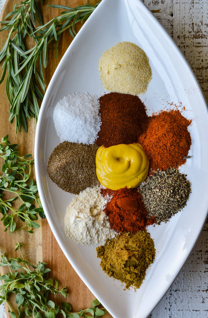 A white diamond shaped plate holding a bunch of different spices with fresh herbs beside it.