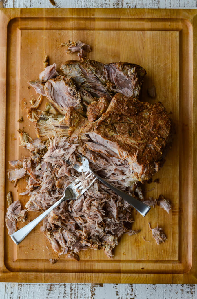 A cooked pork roast with two forks pulling the meat apart on a wooden cutting board.