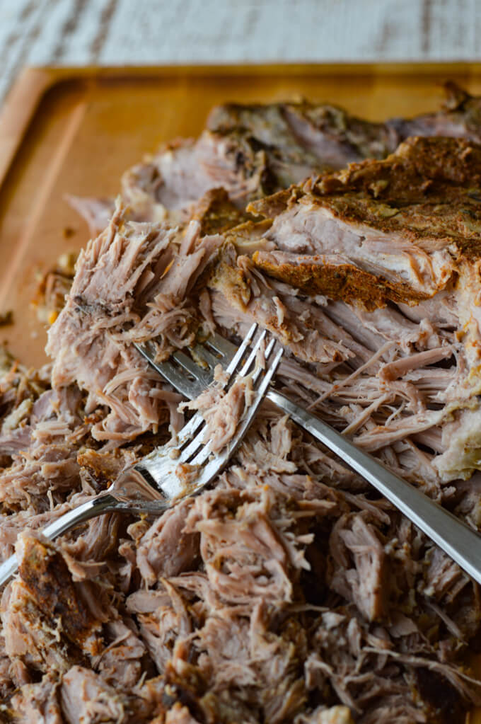 A closeup view of cooked pork roast with two forks pulling the meat apart on a wooden cutting board.
