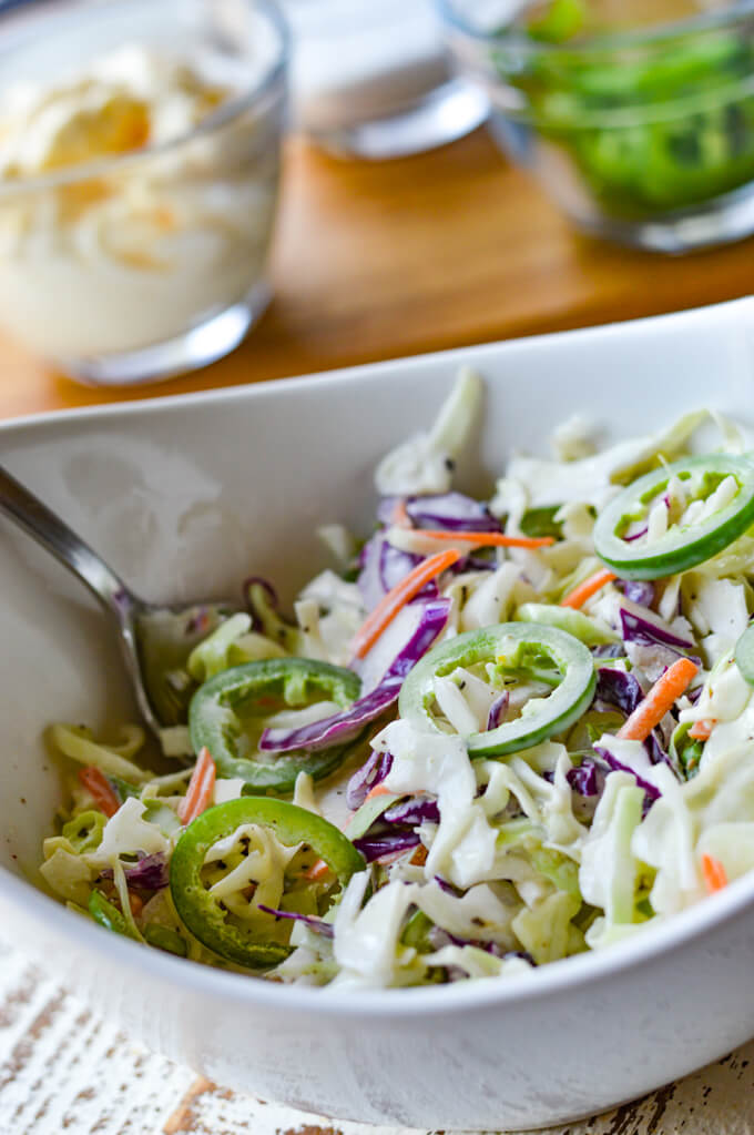 A closeup view of homemade coleslaw in a white bowl with mayo, sliced jalapenos in the background.