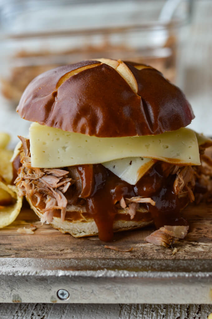 A pulled pork sandwich with bbq sauce and havarti cheese on a wooden tray.