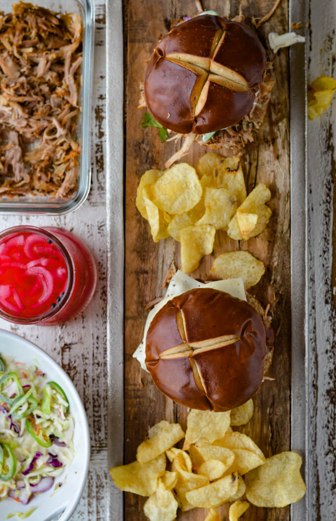 Two Pulled Pork sandwiches with potato chips on a wooden tray with pork, pickled onions and coleslaw beside it.