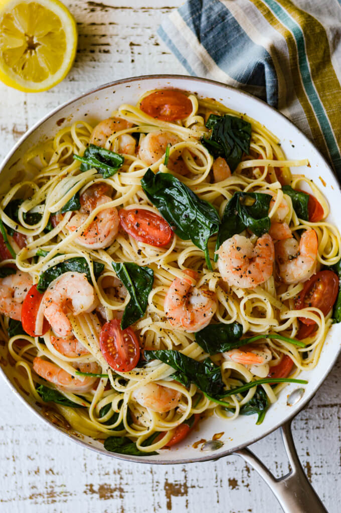 A skillet of shrimp scampi with tomatoes and spinach with a half squeezed lemon and a striped napkin.