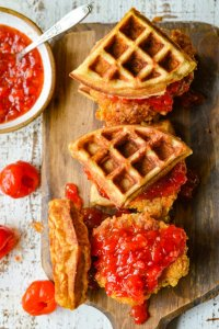Three chicken and waffles with a bowl of peppadew jam and peppadew peppers scatter around.
