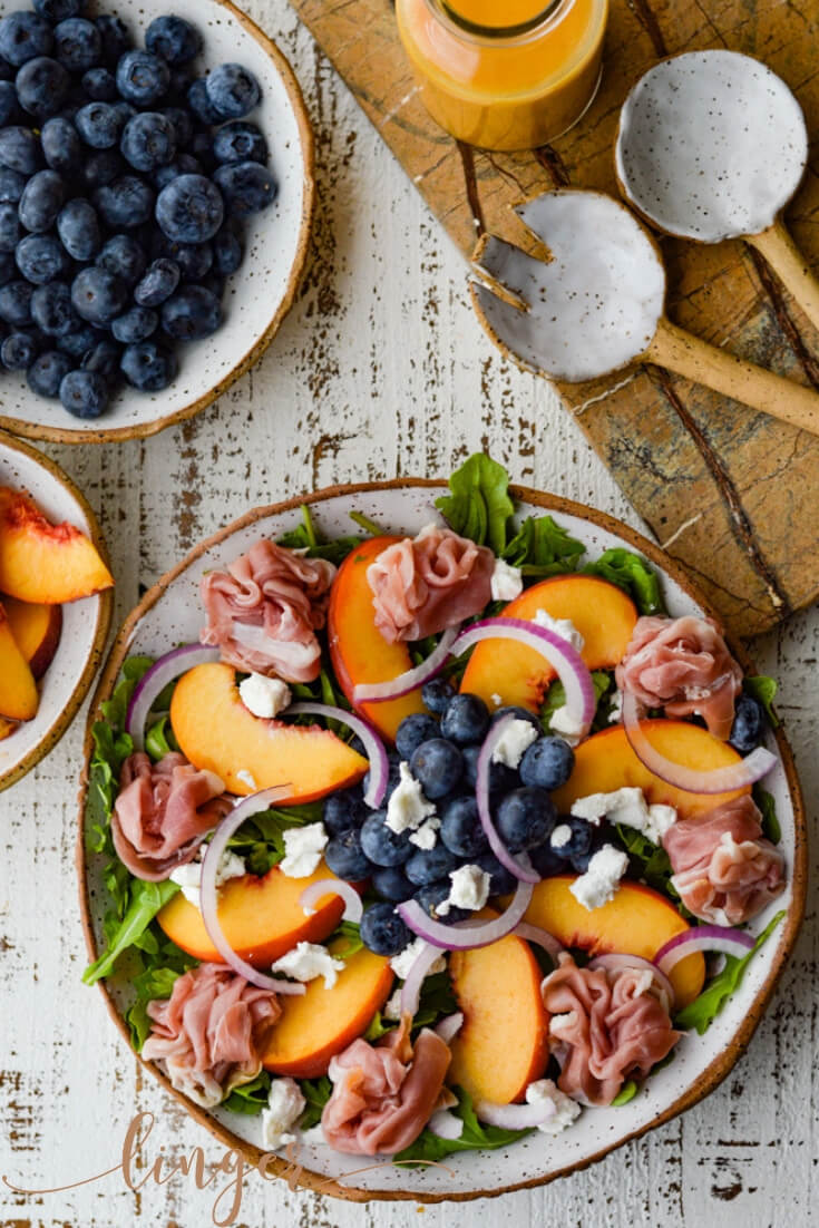 You'll love this simple and healthy recipe - Fresh Peach Arugula Salad. The juiciness of the sweet peaches, the saltiness of the prosciutto, and the creaminess of the goat cheese is the solution for your fall cravings. The dressing is a fresh peach vinaigrette. #saladrecipes #peaches #peachsalad #salad #vinaigrette #saladentrees #prosciutto #goatcheese #blueberries