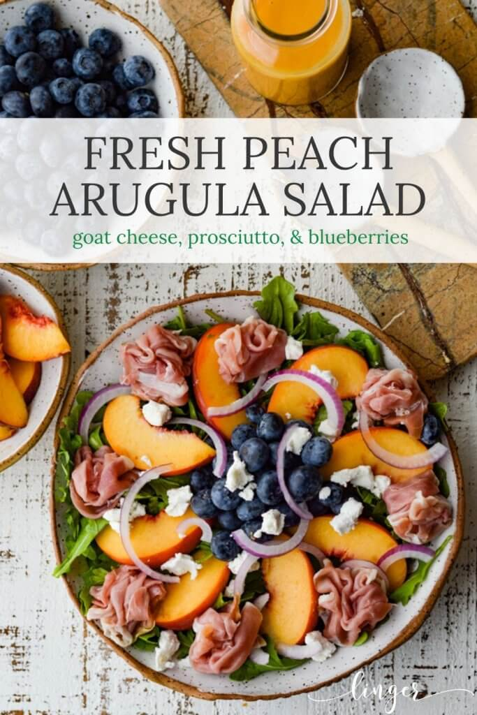 A Peach and Blueberry Arugula Salad in a bowl next to a ceramic salad fork and spoon. A bowl of blueberries and bowl of sliced peaches sit next to it.