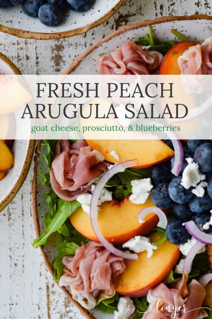 A closeup photo of fresh peach and blueberry arugula salad with prosciutto and goat cheese.