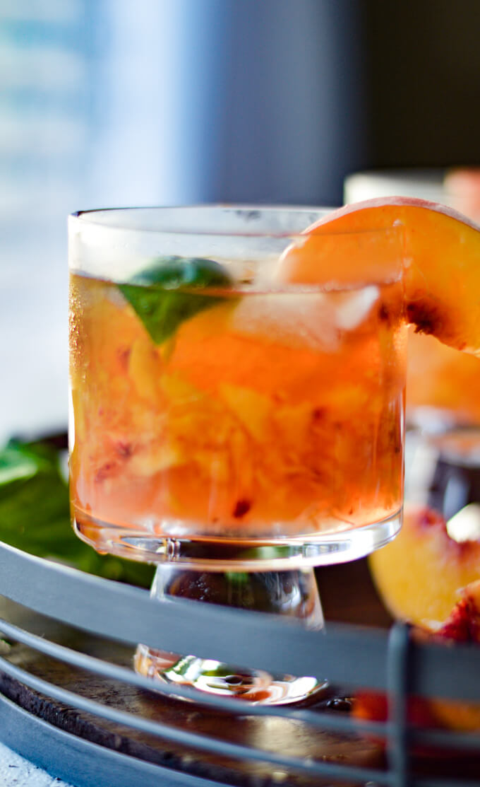 A front view of a peach bourbon cocktail on a round wooden tray with fresh peach slices and fresh basil scattered around.