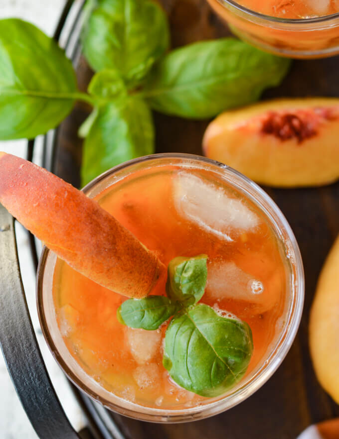 A top view of a peach bourbon cocktail on a wooden traiy with fresh peach slices and fresh basil.