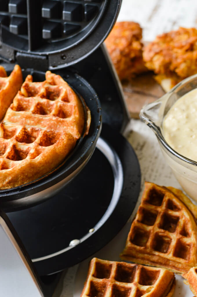 Waffles cooking in a waffle maker with waffles and waffle batter next to them