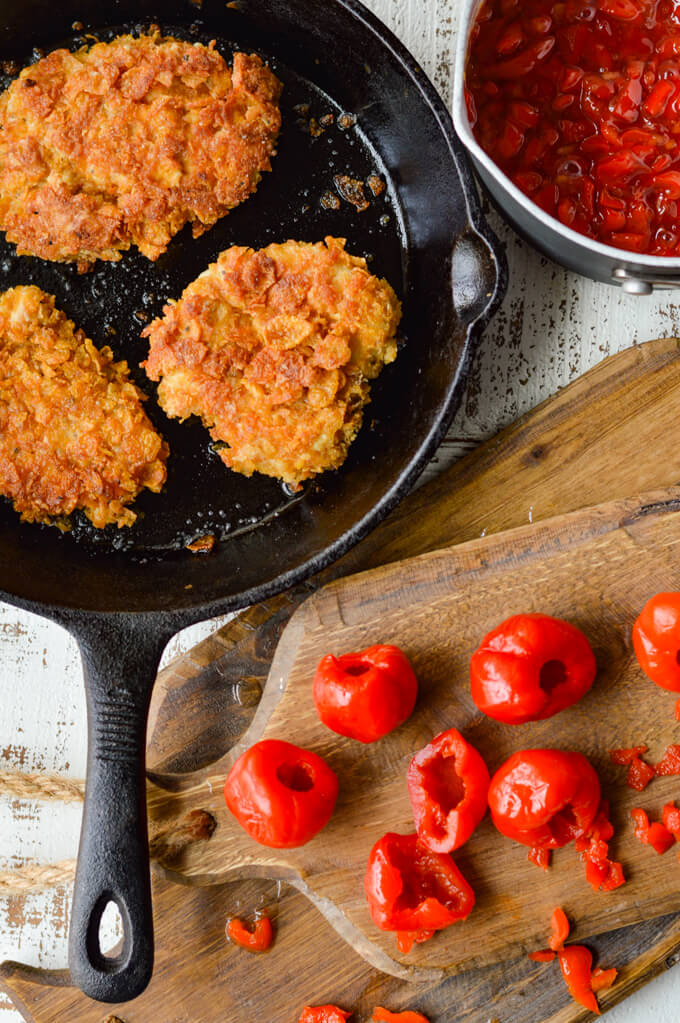 Crispy cooked chicken in a skillet with peppadew sauce in a pan