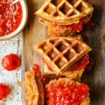 Three chicken and waffles on a board with bowl of peppadew jam and peppadew peppers scattered around.
