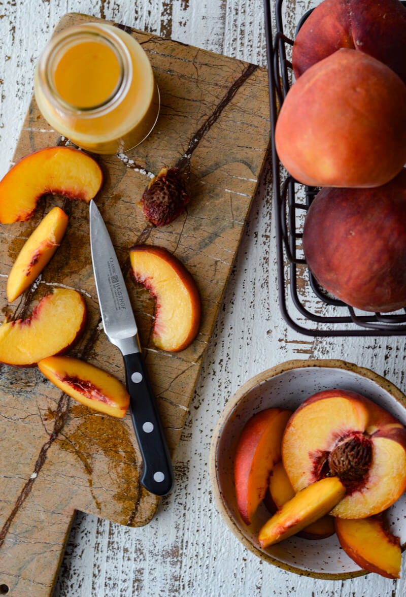 Fresh Peach Arugula Salad with Prosciutto and Blueberries -cutting board with sliced peaches