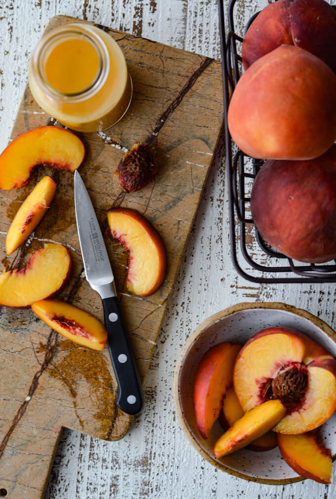Sliced peaches on a cutting board with peach vinaigrette next to it. A basket of peaches and a bowl of halved peaches are next to it as well.