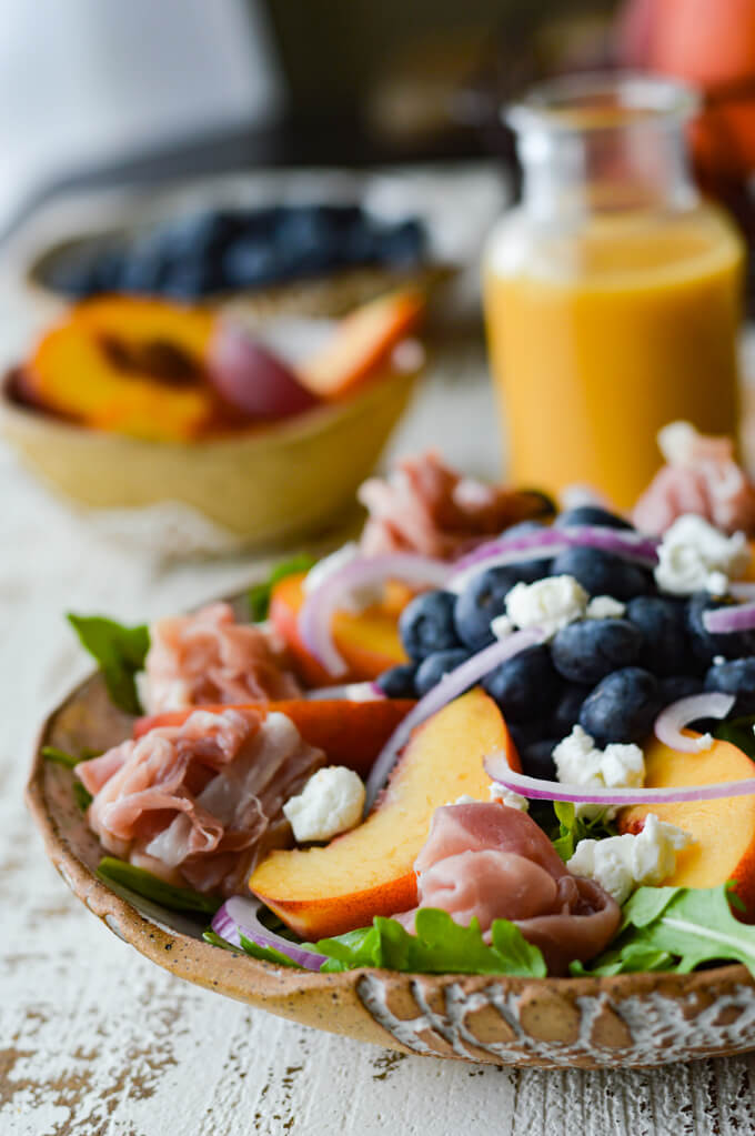 A front view of fresh peach and blueberry arugula with peach vinaigrette and a bowl of peaches and blueberries in the background.