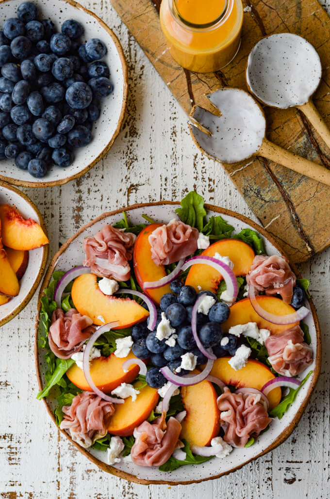 A Peach and Blueberry Arugula Salad in a bowl next ceramic salad fork and spoon. A bowl of blueberries and a bowl of sliced peaches sit next to it.