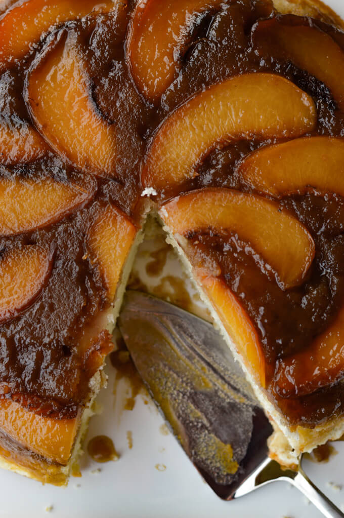 A close-up photo a peach upside down cake wit a cake server in the pan.