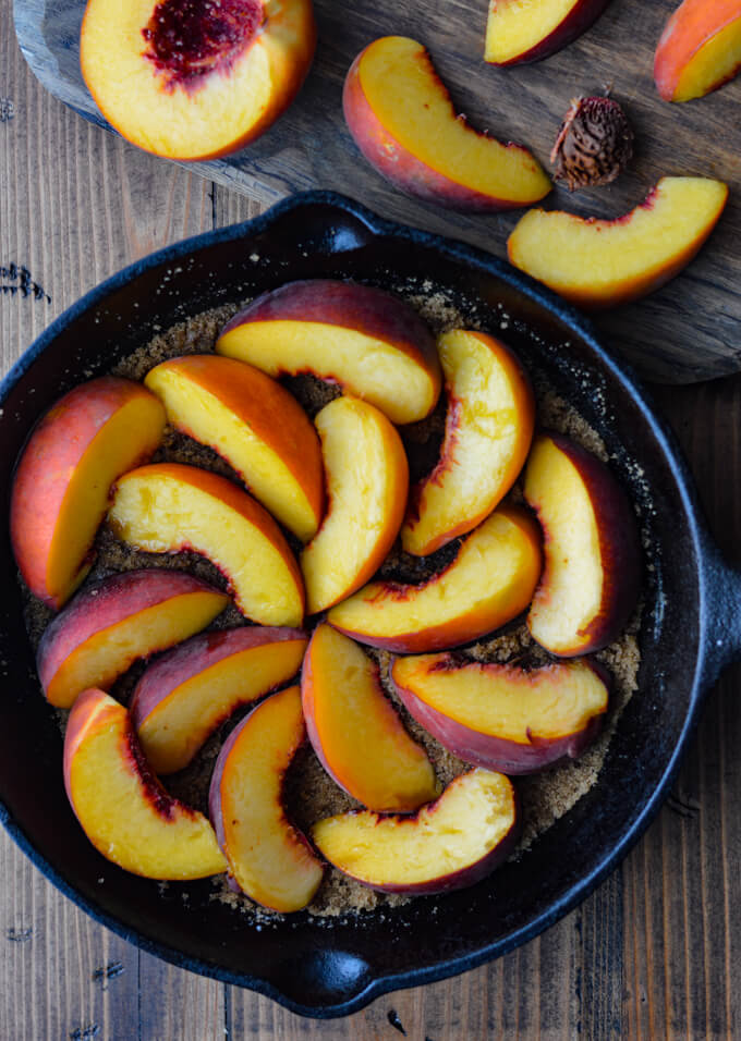 A cast iron pan of brown sugar and butter in the bottom with fresh peach slices arrange in a circular motion on top.