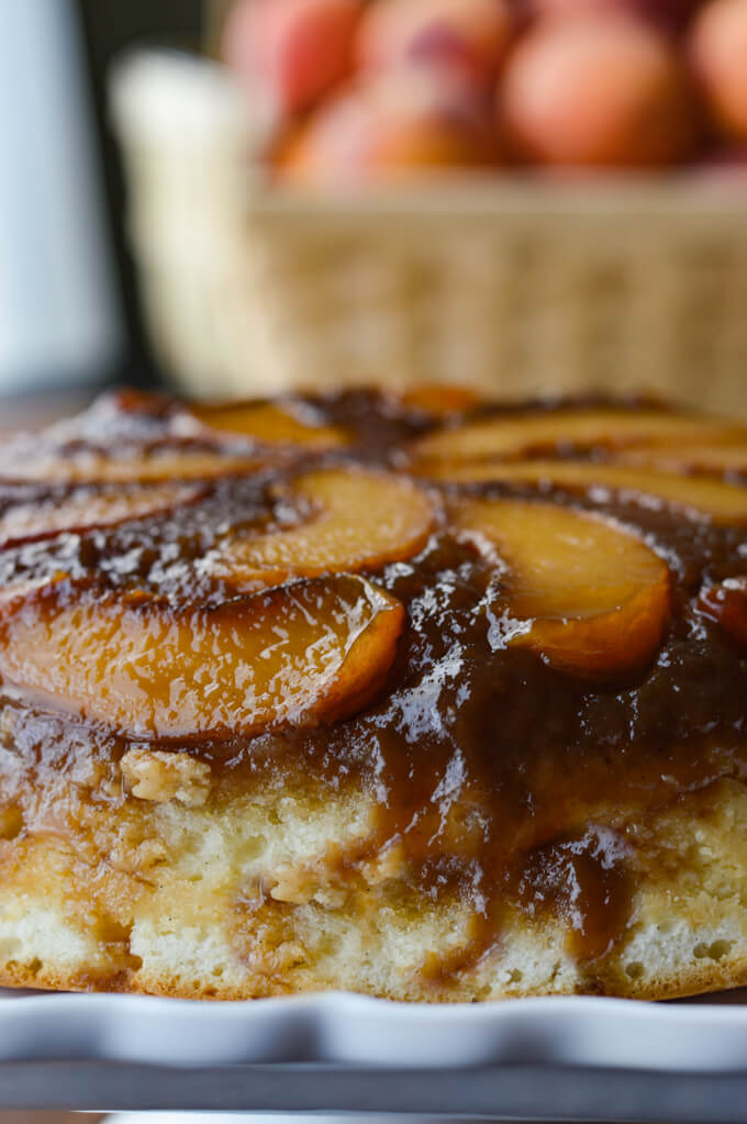 A front view of a peach upside down cake with a basket of peaches in the background.