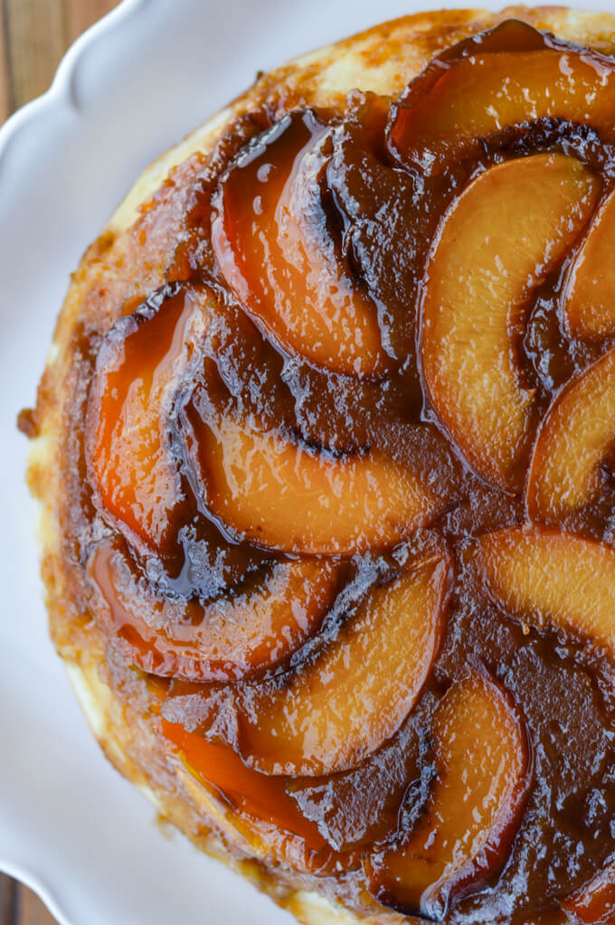 A closeup photo of a peach upside down cake on a white platter.