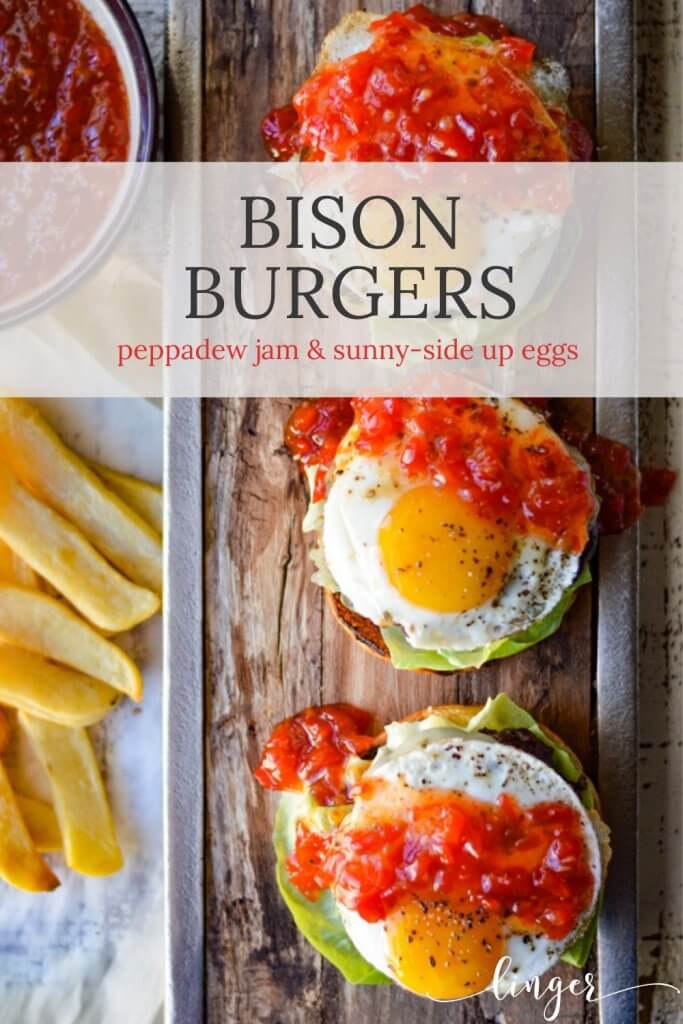 Three cooked bison burgers without the top bun with sunny-side up eggs and peppadew jam on top all on a wooden board next to a bowl of peppadew jam and french fries