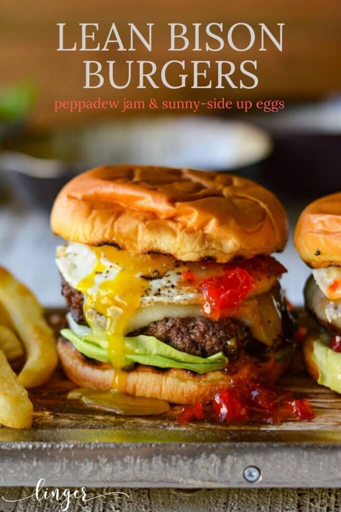 Bison burger with peppadew jam and an over-easy egg on a wooden board with fries next to it