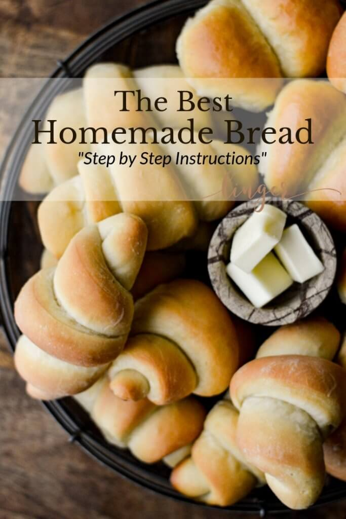 A basket with a bunch of baked crescent shaped bread rolls with butter cubes in the center.